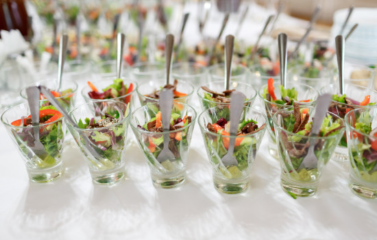 Glasses with salad served on white table